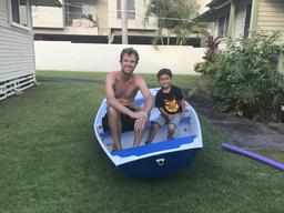 Dave and our neighbor Braden sitting in the nesting dinghy we built.